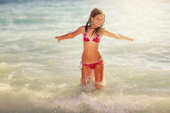 Happy girl jump on the sea waves. In summer vacation Stock Image