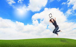 Happy Girl Jump and show touch pad pc Royalty Free Stock Photography