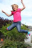 Happy girl jumping. A happy little girl jumping on a trampoline in the garden Stock Images