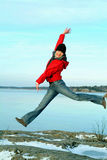 Happy girl jumping. With frozen lake on the background Royalty Free Stock Photo
