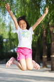 Happy girl jumping. Happy chinese little girl jumping Royalty Free Stock Photography