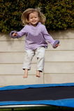 Happy girl jumping. A full body of a beautiful little caucasian white girl child with blond long hair and happy cute expression in her pretty face having great Stock Image