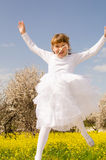 Happy girl jumping. Happy young girl  in white dress jumping and rejoicing in the field of yellow flowers in the spring. Blossom almond at the background Royalty Free Stock Image