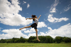 Happy girl jumping. A girl happily jumping on the green grass, under the blue sky Stock Photos