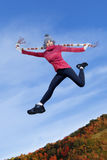 Happy girl jumping on the autumn park Royalty Free Stock Images
