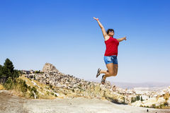 Happy girl jumping on the background of the cave city in Cappado Royalty Free Stock Photo
