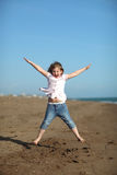 Happy girl is jumping on the beach Royalty Free Stock Image