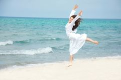 Happy girl jumping on beach Stock Image