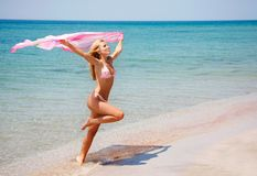 Happy girl jumping on beach Royalty Free Stock Photos