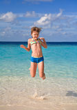 Happy girl jumping on the beach. Little happy girl having fun jumping on the white sandy beach Stock Photography