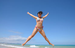 Happy girl jumping on the beach stock photos