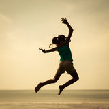 Happy girl jumping on the beach on the day time Royalty Free Stock Images