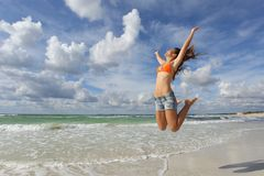Happy girl jumping on the beach on holidays Royalty Free Stock Photos
