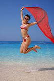 Happy Girl jumping on the beach with scarfs Royalty Free Stock Photography