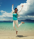 Happy girl jumping on the beach Stock Photos
