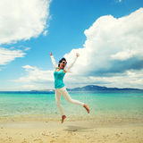 Happy girl jumping on the beach Stock Image