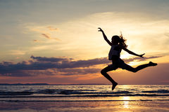 Happy girl jumping on the beach at the sunset time Royalty Free Stock Photography