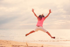 Happy Girl Jumping on the Beach at Sunset Royalty Free Stock Photos