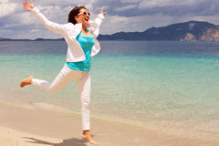 Happy girl jumping on the beach Royalty Free Stock Photo
