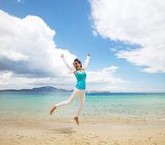 Happy girl jumping on the beach Royalty Free Stock Image