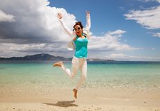 Happy girl jumping on the beach Stock Photo