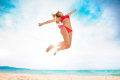 Happy Girl jumping on the beach. Young pretty hot woman on the tropic island jumping in summer near the sea. Young caucasian woman near ocean beach royalty free stock photography