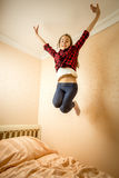 Happy girl jumping on bed at morning Royalty Free Stock Photos