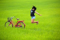 Happy Girl Jumping Beside Bike In Paddy Field Stock Photos