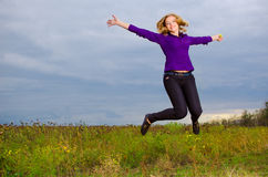 Happy girl jumping. Happy blondie girl jumping outdoor Stock Image