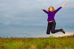 Happy girl jumping. Happy blondie girl jumping outdoor royalty free stock photography