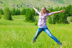 Happy girl jumping on the field Royalty Free Stock Photos