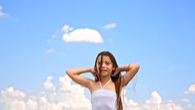 Happy Girl Jumping. In the frame there is a happy pretty little girl with long brown hair in white sundress jumping with joy raising hands enjoying summertime on stock video
