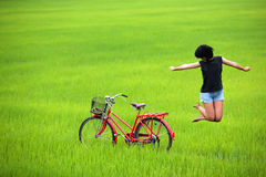 Happy girl jumping in green field Royalty Free Stock Photography