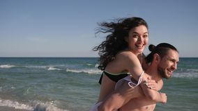 Happy girl jumping on guy`s back, love couple on Summer vacation, wind develops hair, tropics, along ocean coast,. On background beautiful beach, travel, slow stock footage