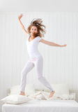Happy girl jumping and having fun in bed Royalty Free Stock Photos