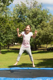 Happy girl jumping high on trampoline in park Stock Image