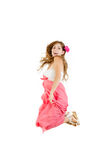 Happy girl jumping of joy in pink dress with flower Stock Photography