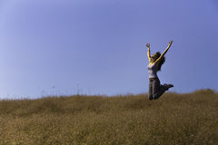 Happy girl jumping in a meadow Royalty Free Stock Image