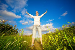 Happy girl is jumping over the blue sky Royalty Free Stock Image
