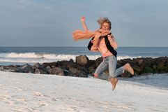 Happy girl jumping playfully on beach in autumn. Stock Image