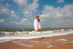 Happy girl jumping on the sunny beach Royalty Free Stock Image