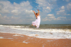 Happy girl jumping on the sunny beach Royalty Free Stock Photo