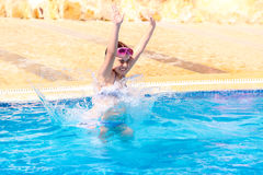 Happy girl jumping to the pool Stock Images