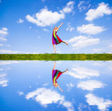 Happy girl jumping together on green meadow. Against the backdrop of blue sky. Reflected in water Stock Images