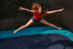 Happy girl jumping on trampoline with enclosure. Top view portrait of teenage girl jumping on trampoline with enclosure outdoors stock photography