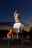 Happy Girl Jumping. A young, blond girl with a big smile jumps off of a bench a sunset.  Her little brother climbs up behind her with a funny expression.  The Stock Photography