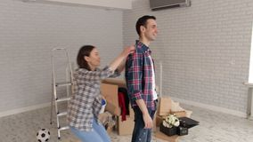 Happy cheerful couple having fun in new apartment. A happy girl jumps on the back of her cheerful guy in a new apartment among the boxes. Young couple moving in stock footage