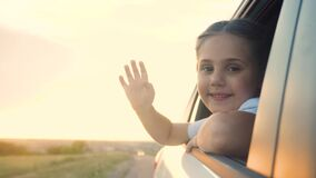 Happy girl kid child smile leaned out of a car window waving hand. Happy family travel journey concept. Daughter sister