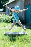Happy girl kid jumping in the trough Royalty Free Stock Photo