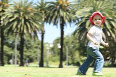 Happy girl kid running in park outside. Girl running in park with background of palm trees and grass Royalty Free Stock Image